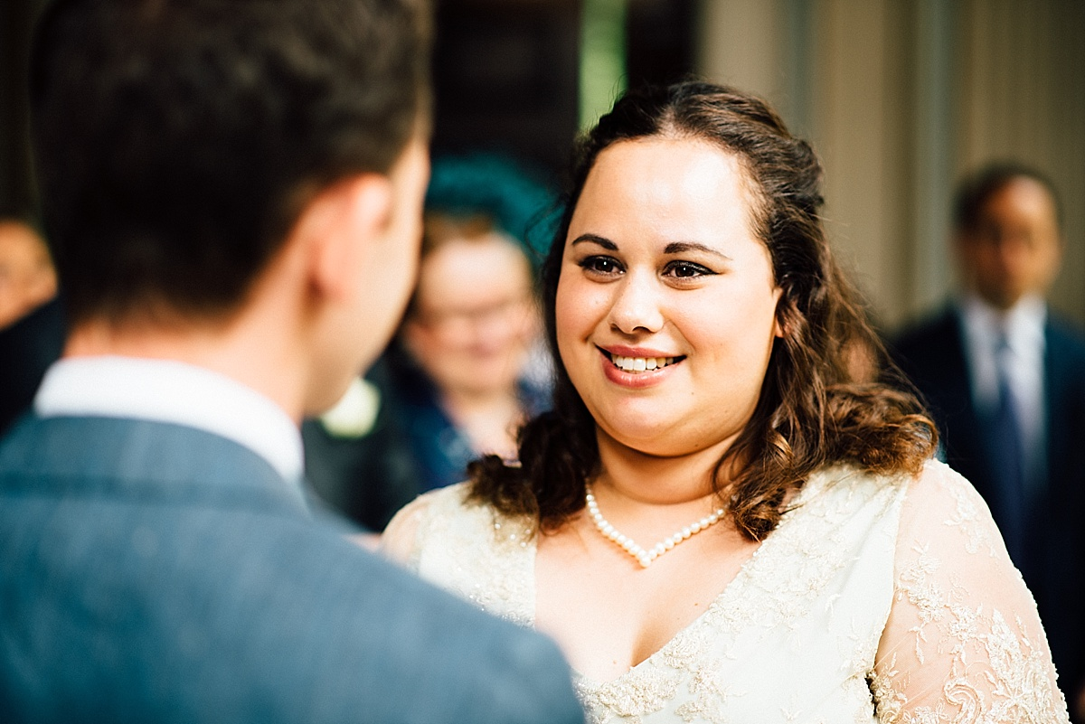 fun wedding photography bride looks at groom during ceremony