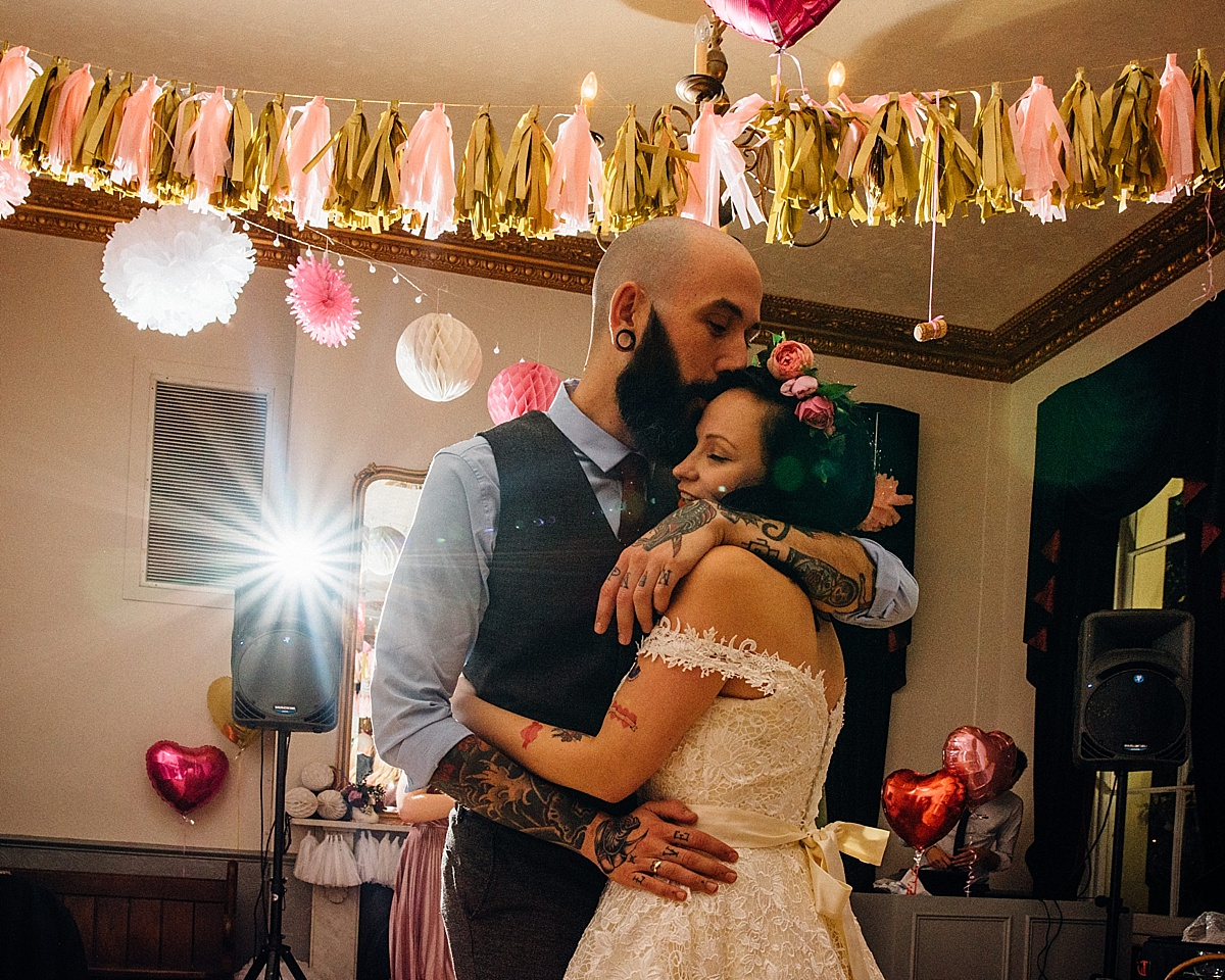 fun wedding photography tattooed groom hugs bride wearing flower crown in pub