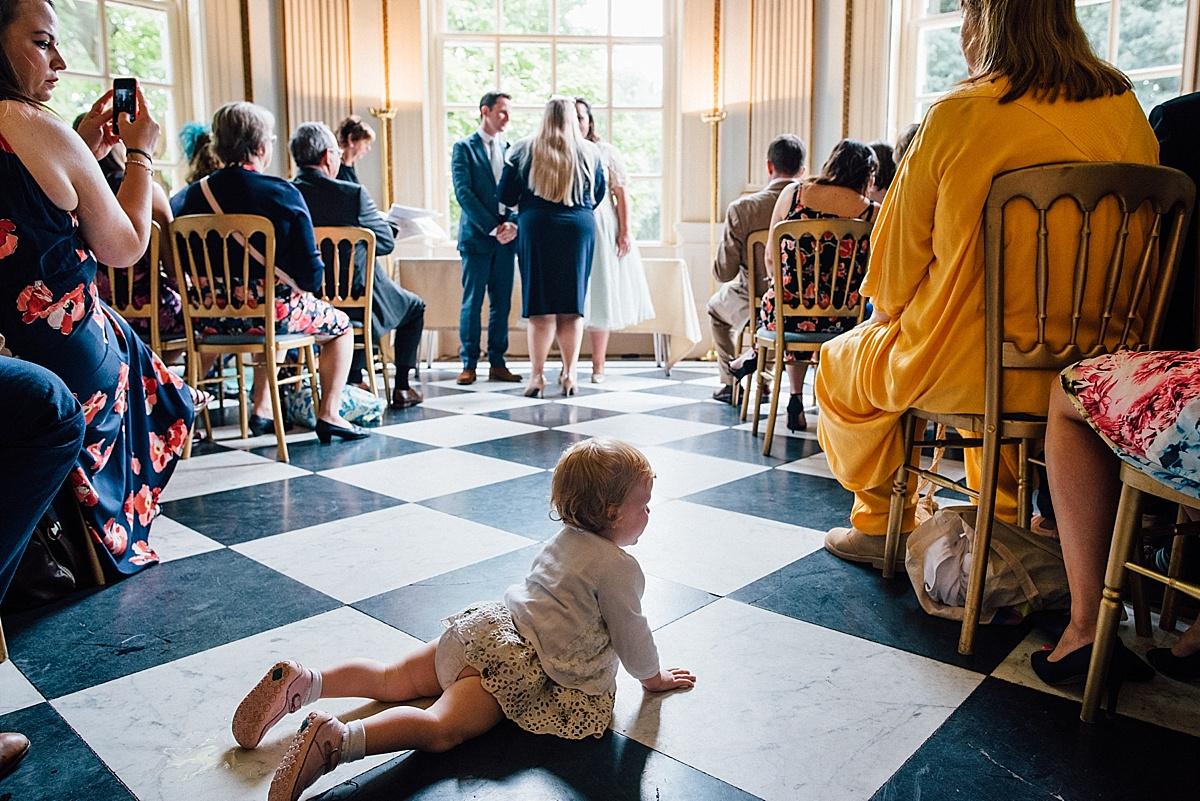 fun wedding photography toddler lies in aisle during wedding ceremony