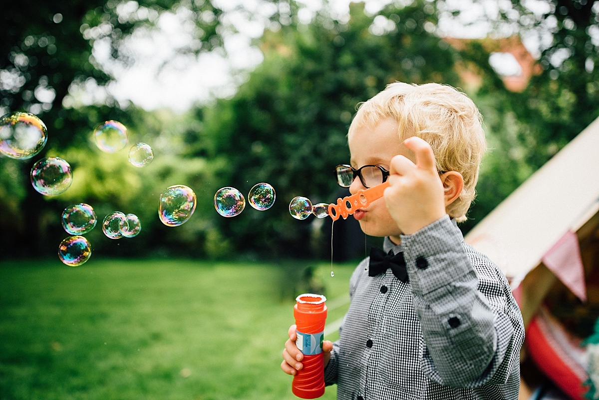 fun wedding photography little boy blows bubbles