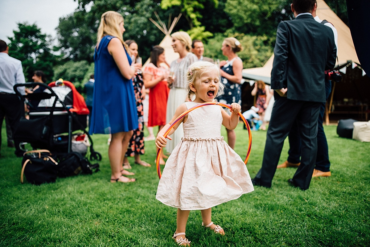 fun wedding photography little girl plays at garden wedding