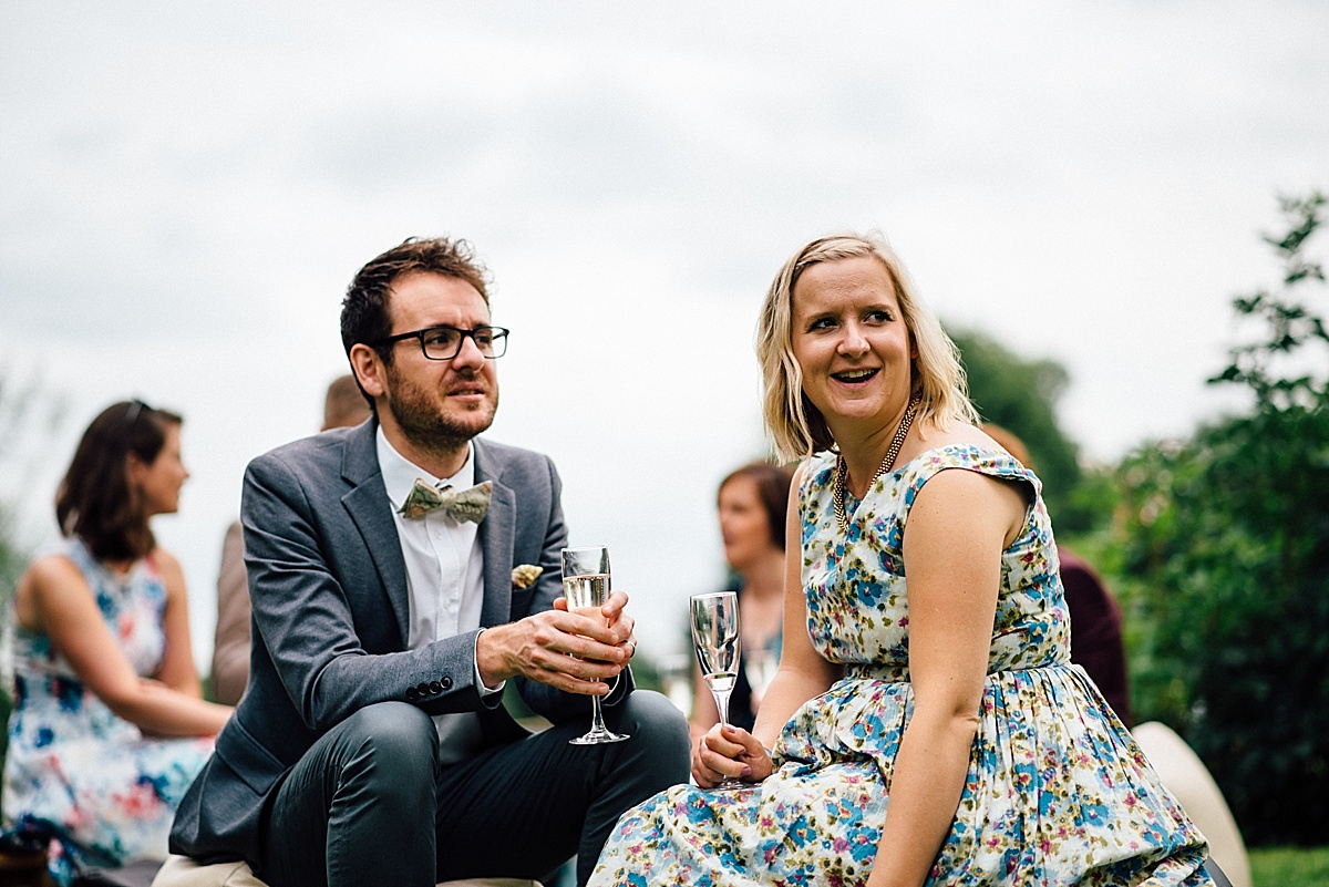 fun wedding photography guests enjoy prossecco at garden wedding