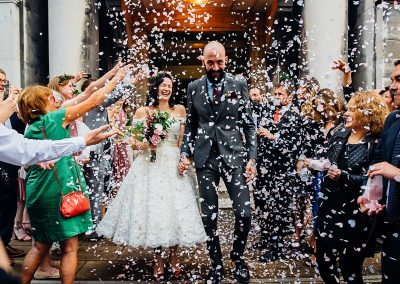 bride and groom outside townhall covered in confetti taken by Parrot & Pineapple Wedding Photography