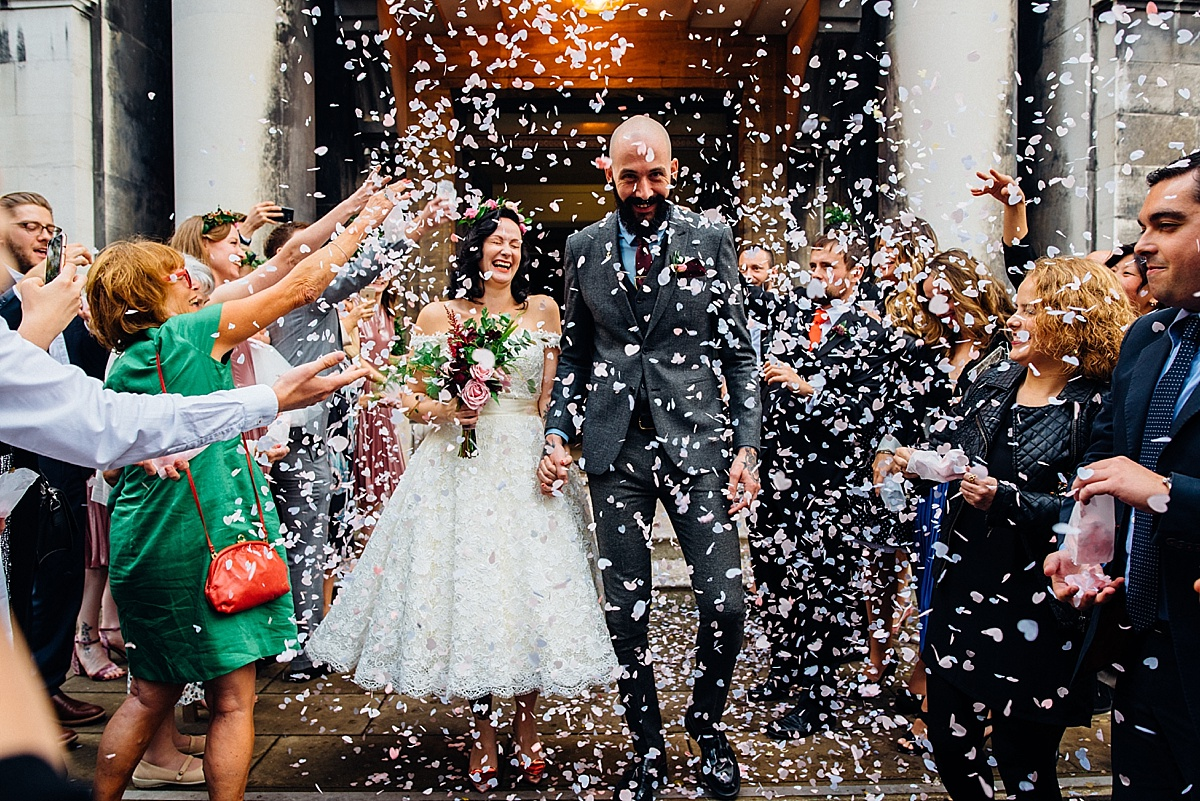 Bride and Groom showered in confetti as they leave wedding venue in London