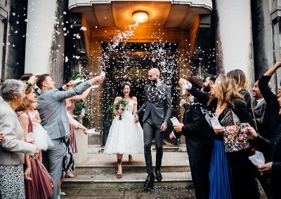 bride and groom leave town hall and confetti being thrown taken by Parrot & Pineapple Wedding Photography