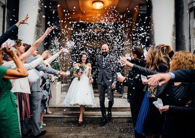Bride and Groom covered in confetti leaving london town hall taken by Parrot & Pineapple Wedding Photography