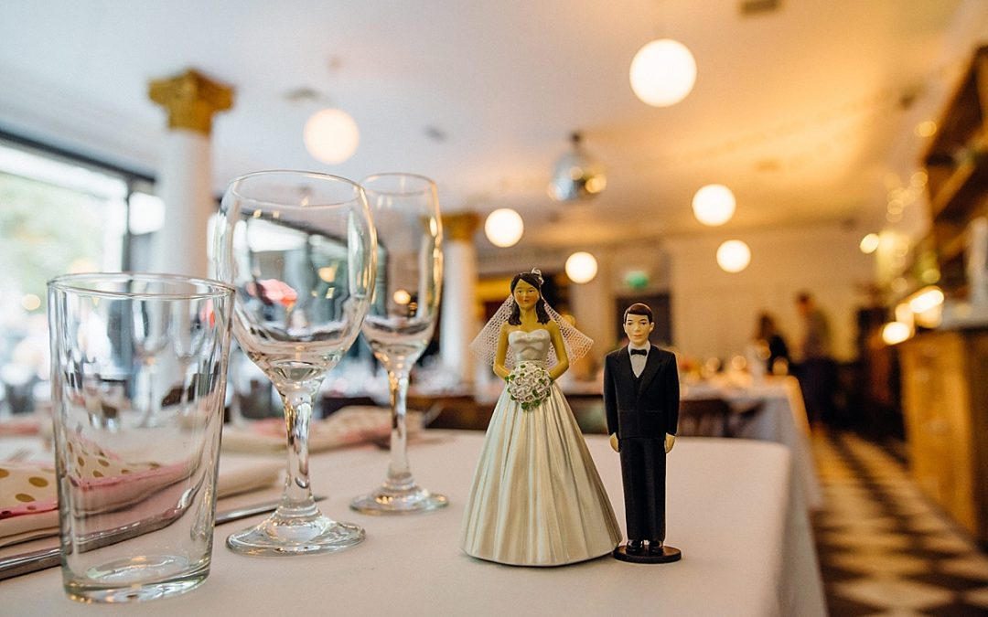 tall bride and short groom figurine on table at pub wedding taken by Parrot & Pineapple Wedding Photography