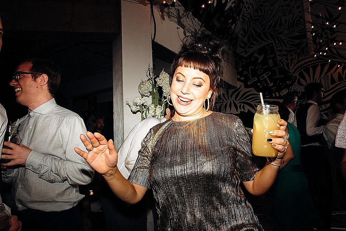 fun wedding photography-gold bridesmaid with jamjar cocktail