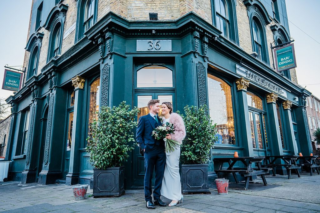 bride and groom stand outside East london pub wedding venue the londesborugh