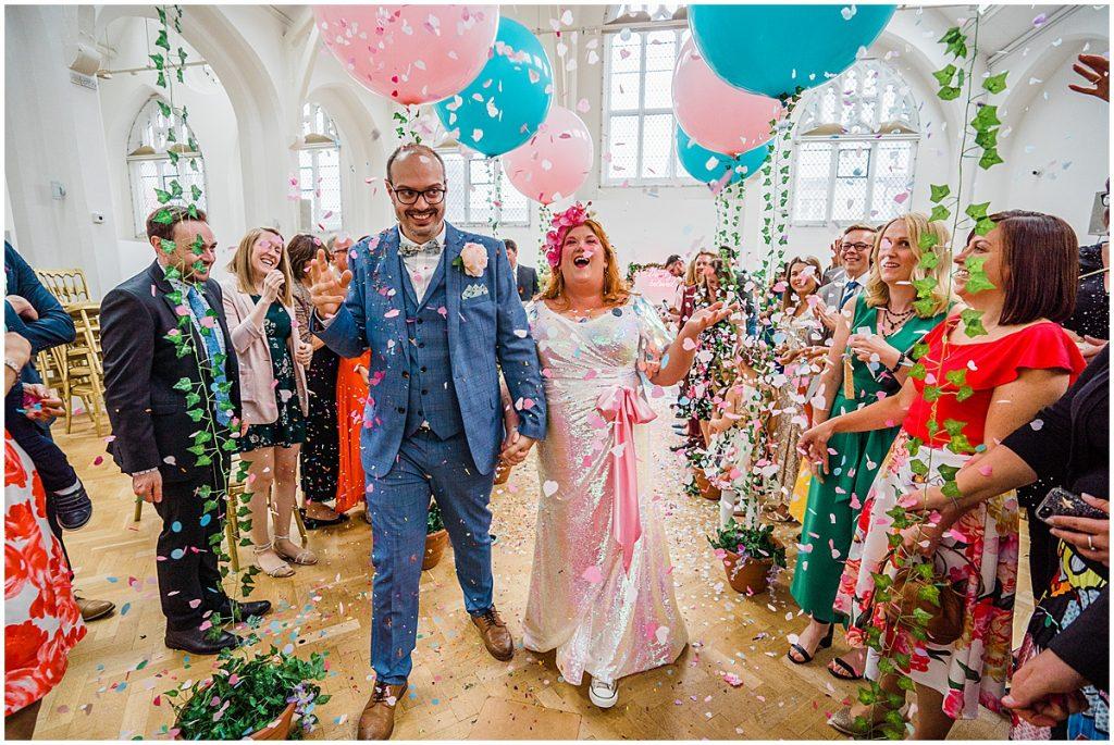 bride sequin wedding dress and groom walk through confetti at The Old Library Birmingham. Parrot and Pineapple.