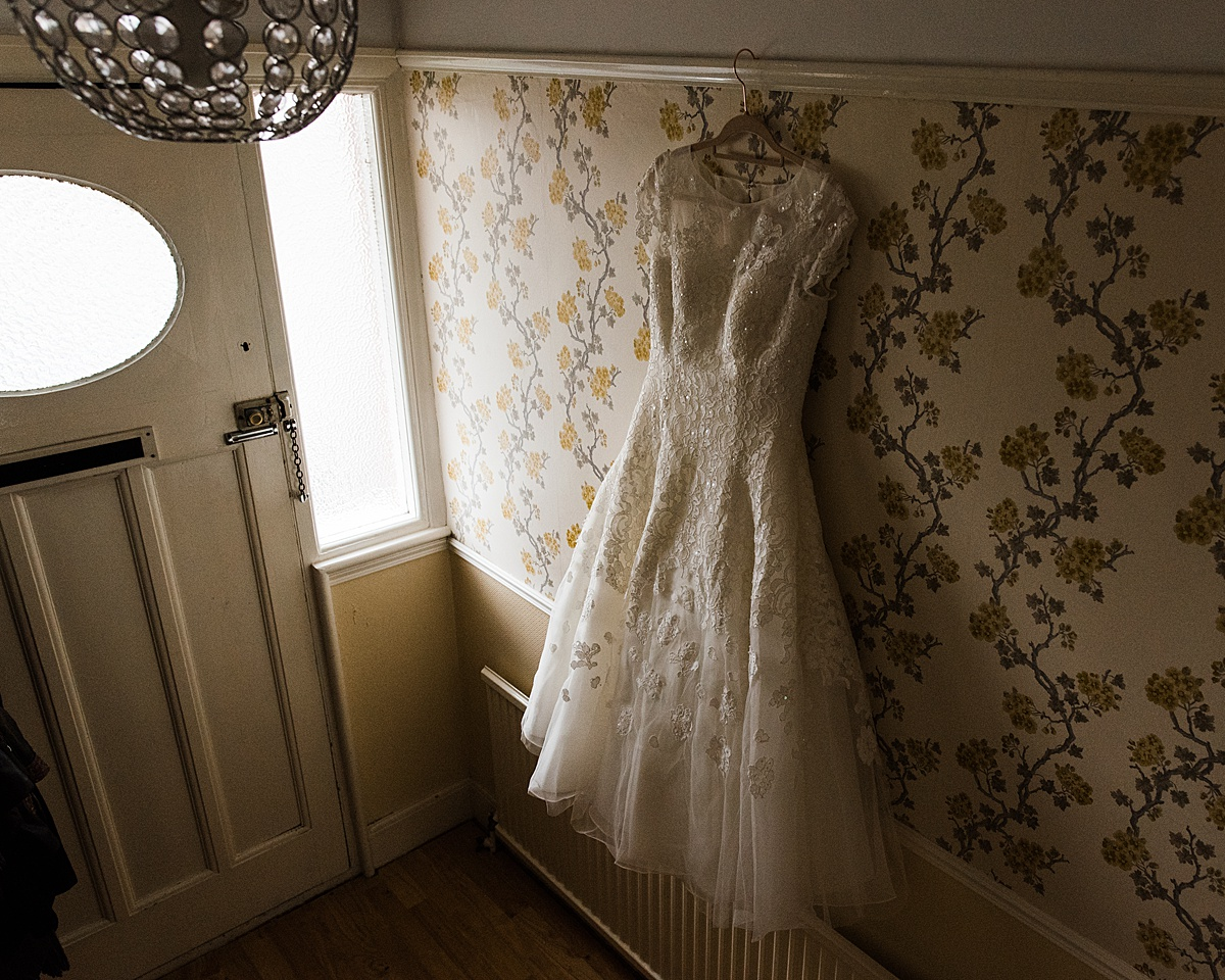Kat's wedding dress hanging in the hallway ready to be worn - Photo taken by Parrot and Pineapple Wedding Photography