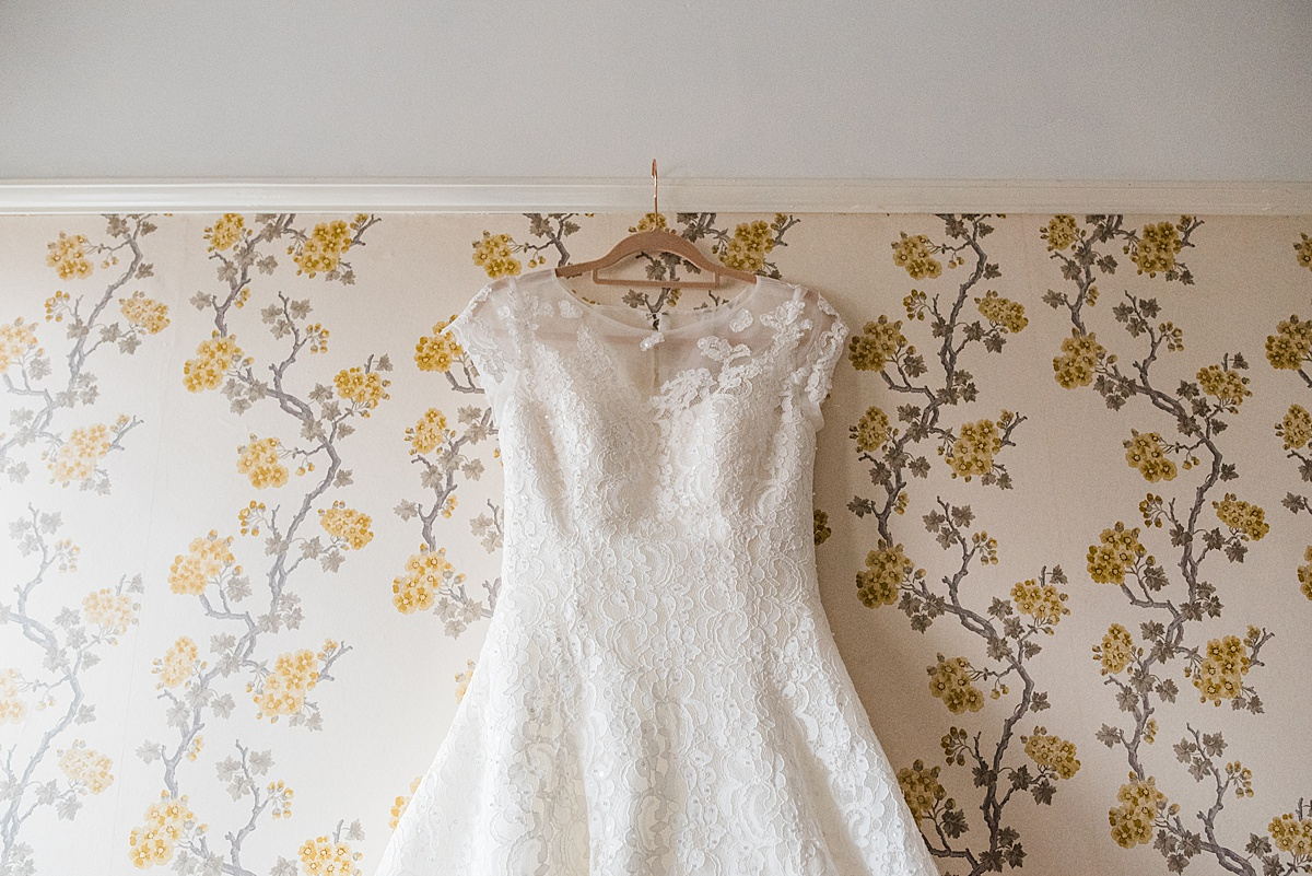 A close up of the wedding dress hanging against vintage inspired wallpaper - Photo taken by Parrot and Pineapple Wedding Photography