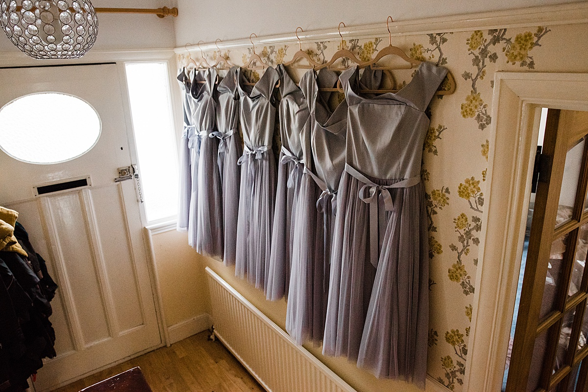 Kat's bridesmaid dresses hanging in the hallway - Photo taken by Parrot and Pineapple Wedding Photography