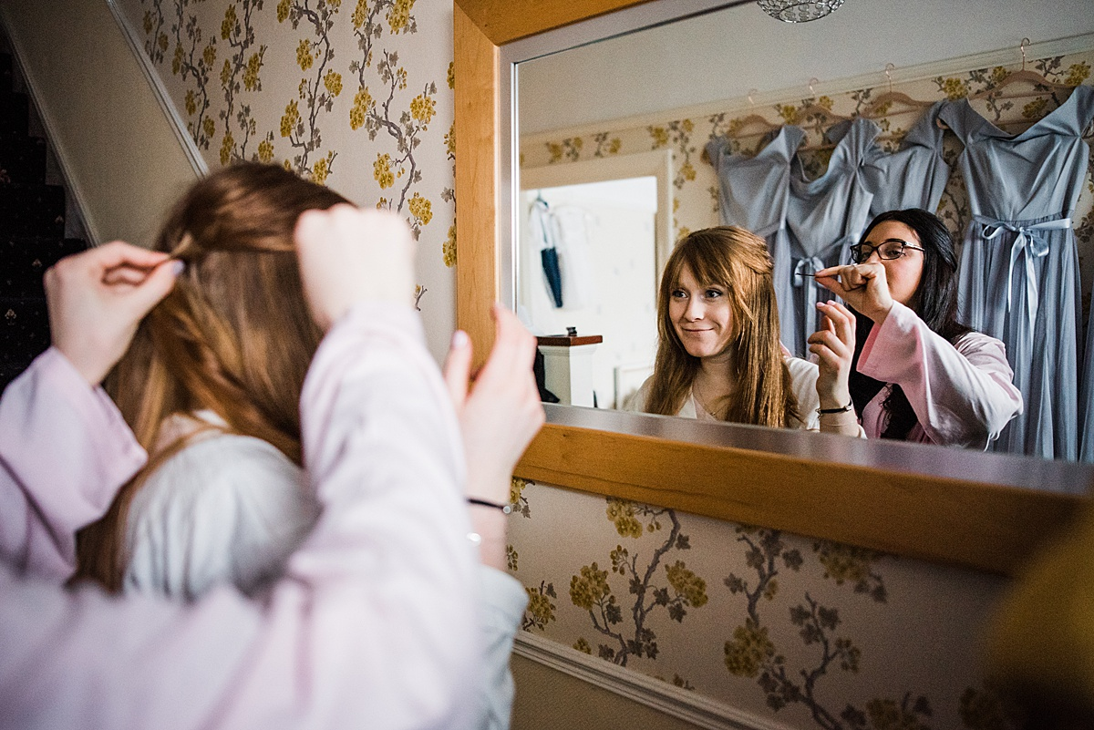 Kat's bridesmaid helps her get her hair ready looking in the mirror - Photo taken by Parrot and Pineapple Wedding Photography