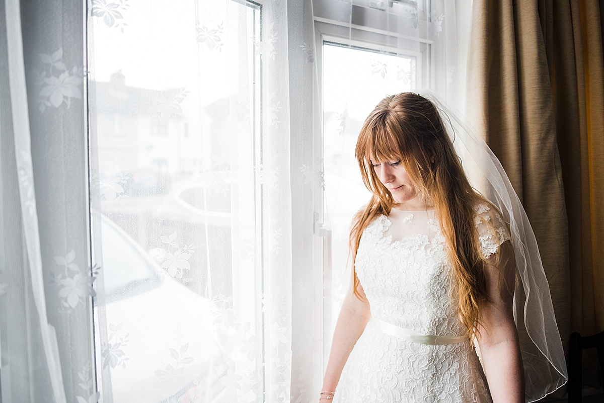 Kat standing by the window in her wedding dress - Photo taken by Parrot and Pineapple Wedding Photography