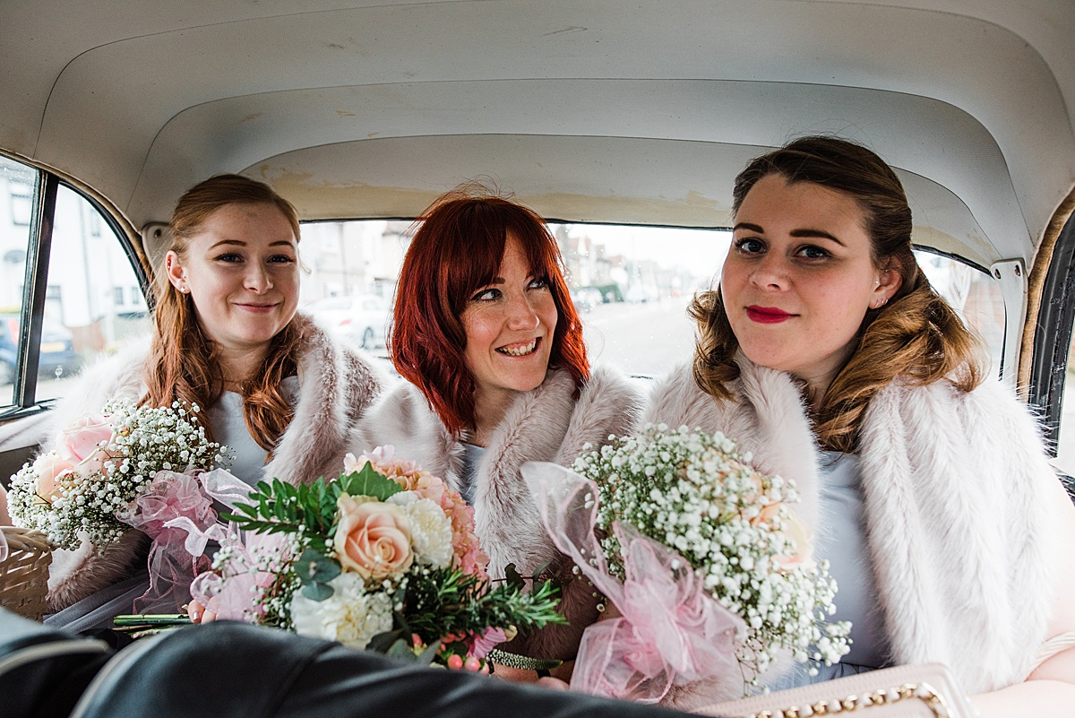 The bridesmaids in the wedding car smiling at the camera - Photo taken by Parrot and Pineapple Wedding Photography