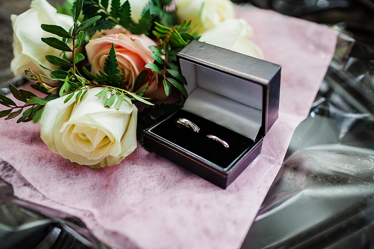The wedding rings in their box next to the button holes - Photo taken by Parrot and Pineapple Wedding Photography