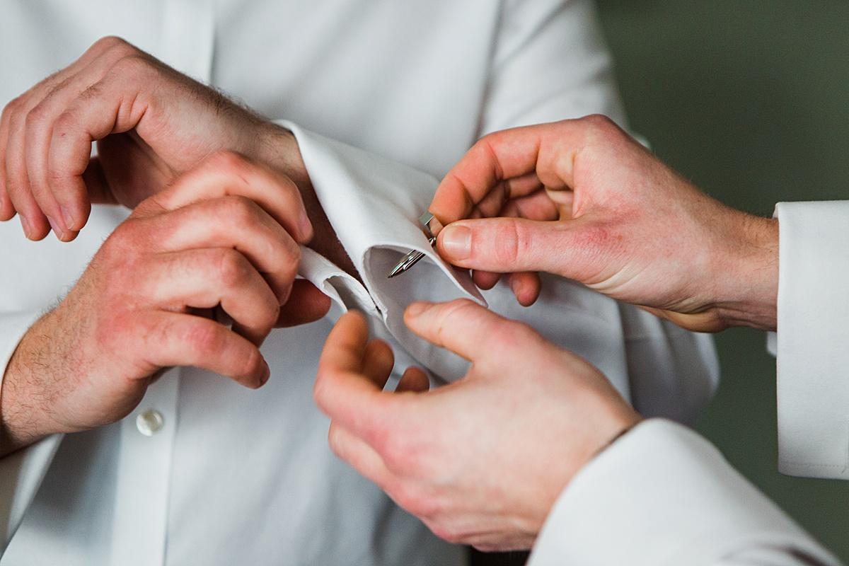 Groomsman helping the groom put his cufflinks on - Photo taken by Parrot and Pineapple Wedding Photography