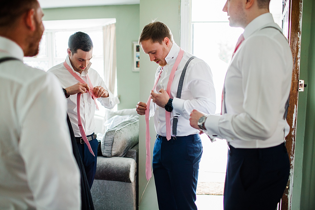 The Groomsmen putting their ties on - Photo taken by Parrot and Pineapple Wedding Photography