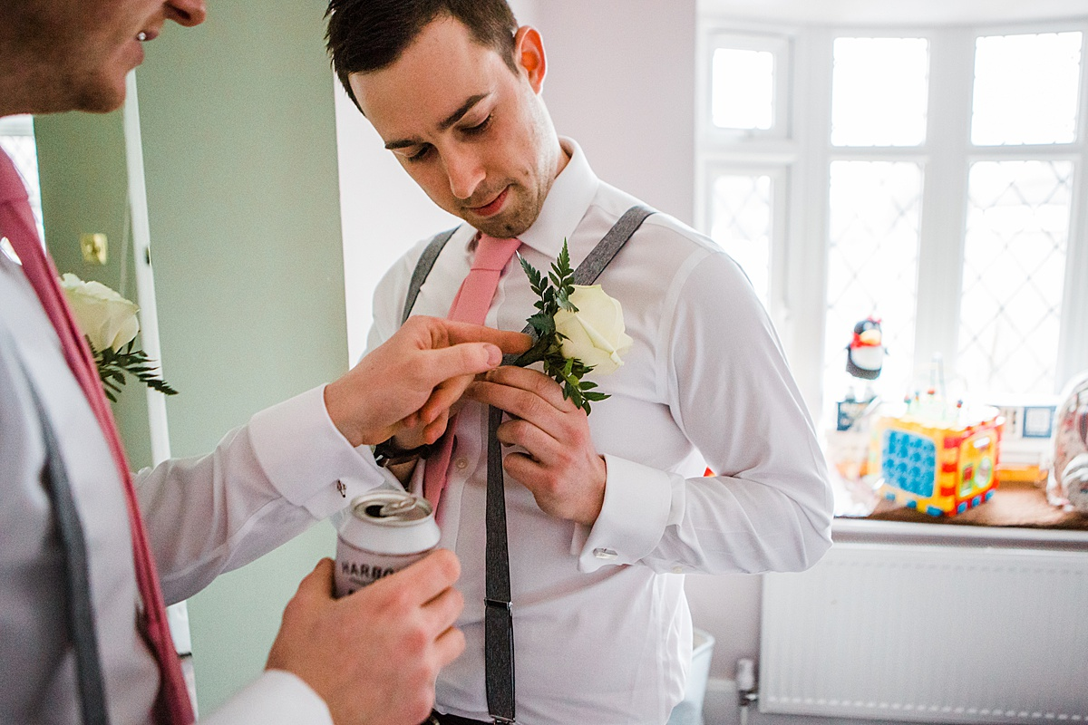 A Groomsman having his buttonhole put on by his friend - Photo taken by Parrot and Pineapple Wedding Photography