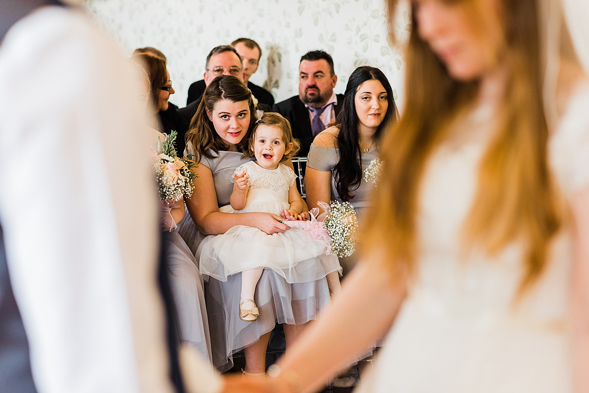 Kat and Aaron's daughter sitting on a bridesmaid lap smiling at her mummy and daddy - Photo taken by Parrot and Pineapple Wedding Photography