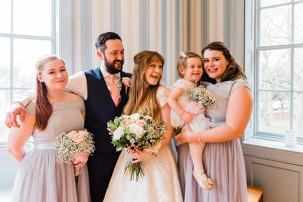 Kat and Aaron standing with their bridesmaid and their daughter smiling - Photo taken by Parrot and Pineapple Wedding Photography