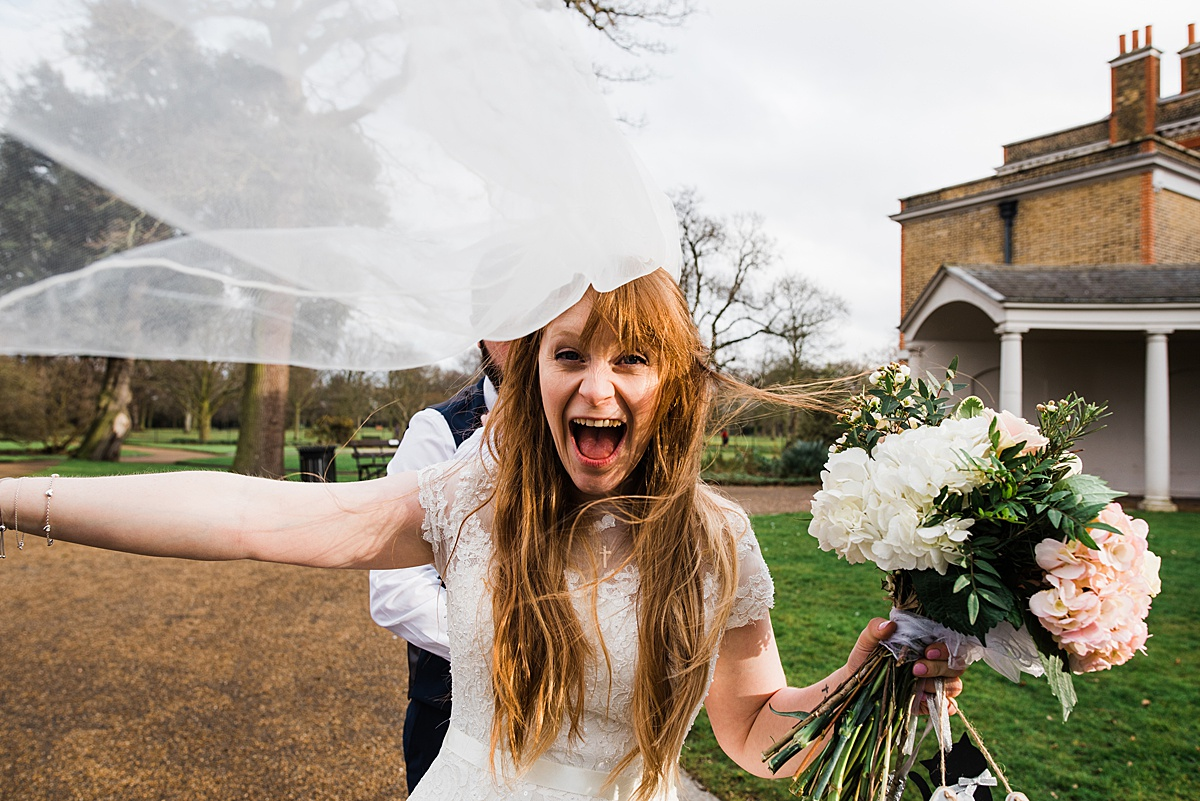 Kat cheering at the camera with her bouquet, veil blowing in the wind- Photo taken by Parrot and Pineapple Wedding Photography
