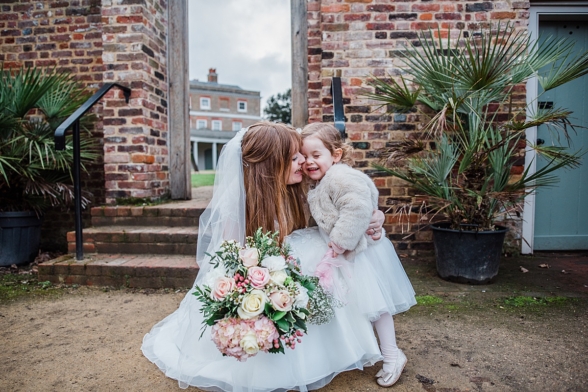 Kat cuddling her daughter outside the wedding venue - Photo taken by Parrot and Pineapple Wedding Photography