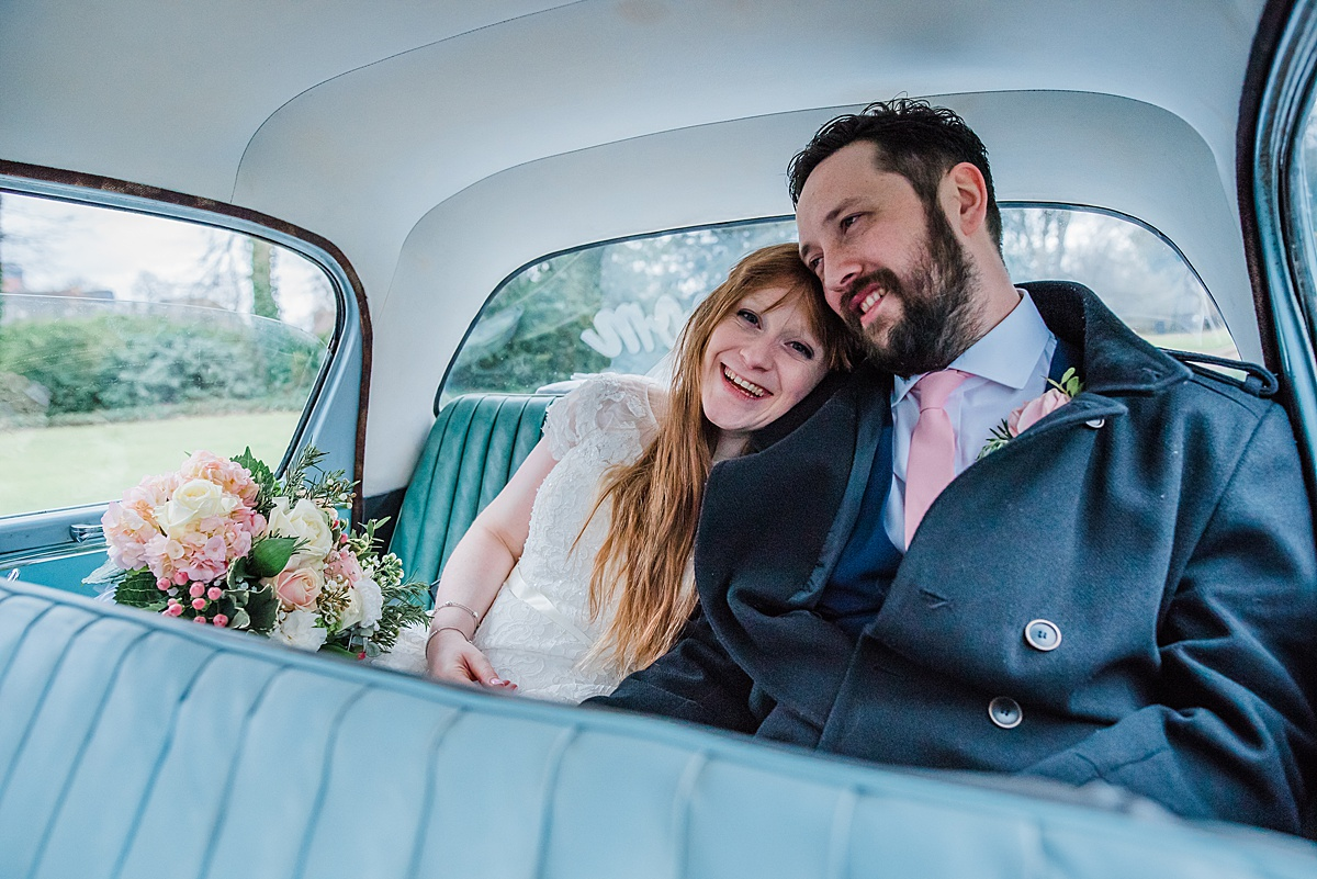 The bride and groom in their vintage wedding car smiling - Photo taken by Parrot and Pineapple Wedding Photography