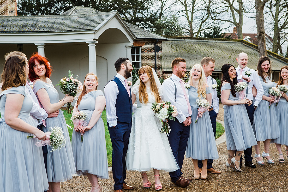 The bridal party having a laugh outside the wedding venue smiling to each other - Photo taken by Parrot and Pineapple Wedding Photography