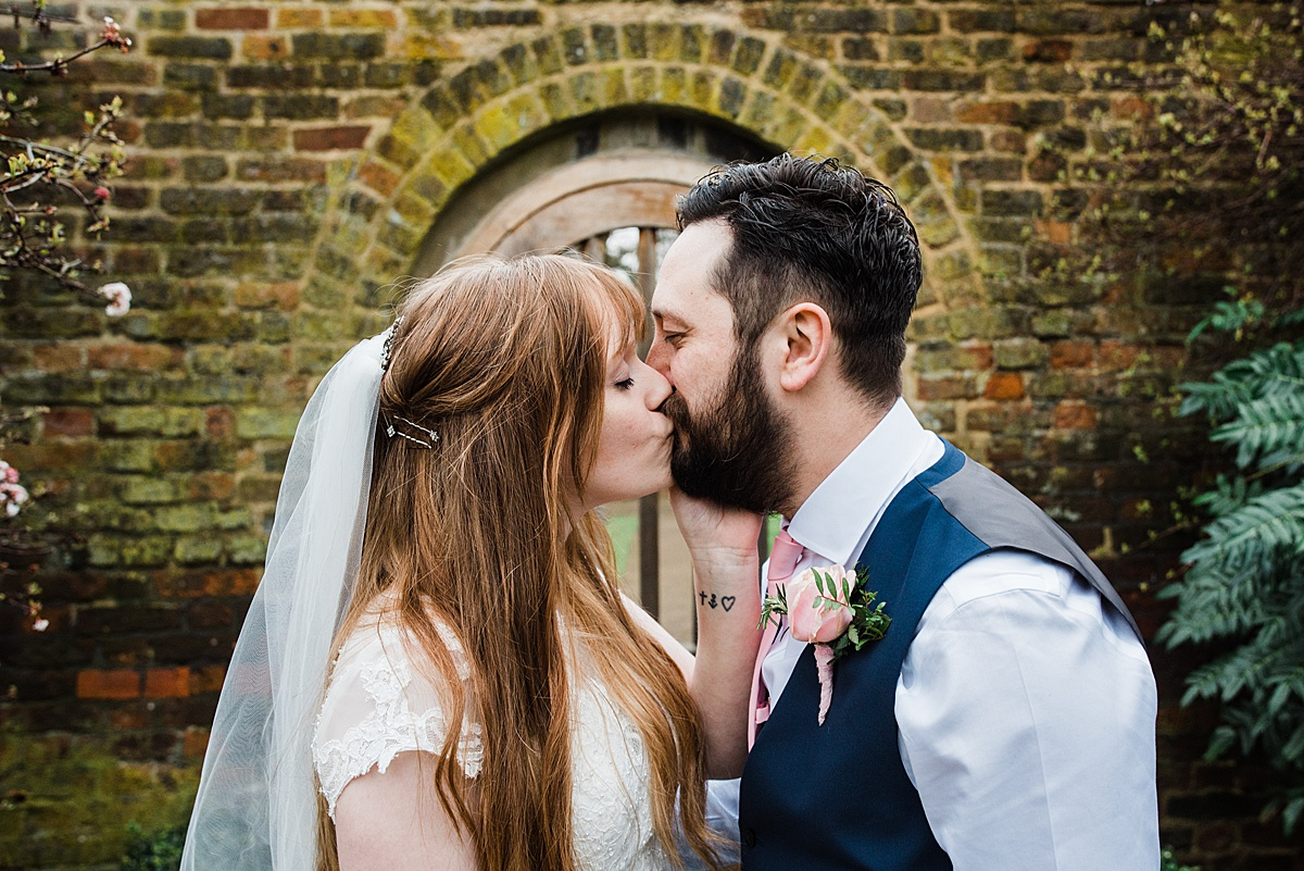 Bride and Groom share a kiss in the garden at the wedding venue - Photo taken by Parrot and Pineapple Wedding Photography