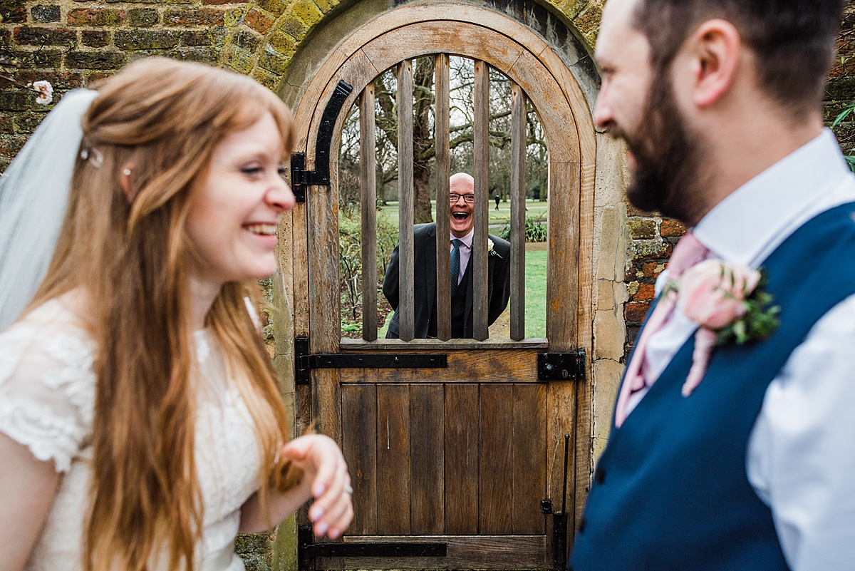 Family member pops his face threw the garden gate making wedding couple laugh - Photo taken by Parrot and Pineapple Wedding Photography