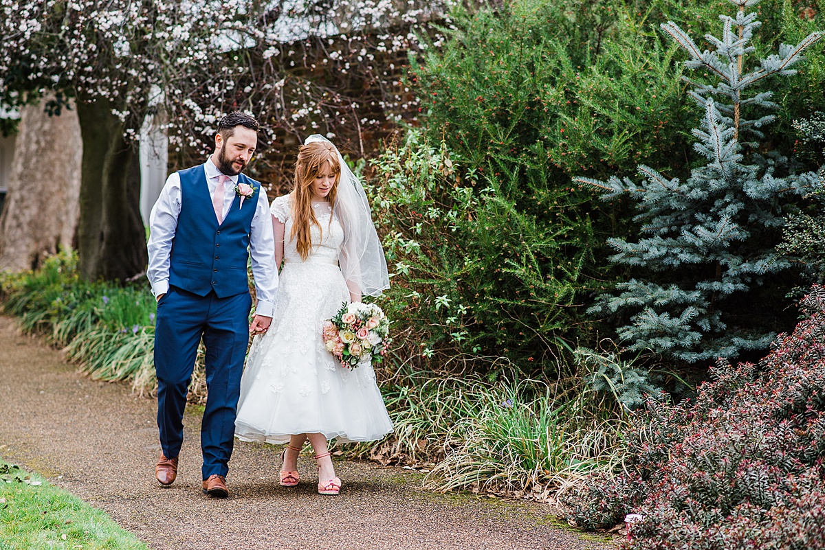 Bride and Groom taking a stroll in the garden - Photo taken by Parrot and Pineapple Wedding Photography