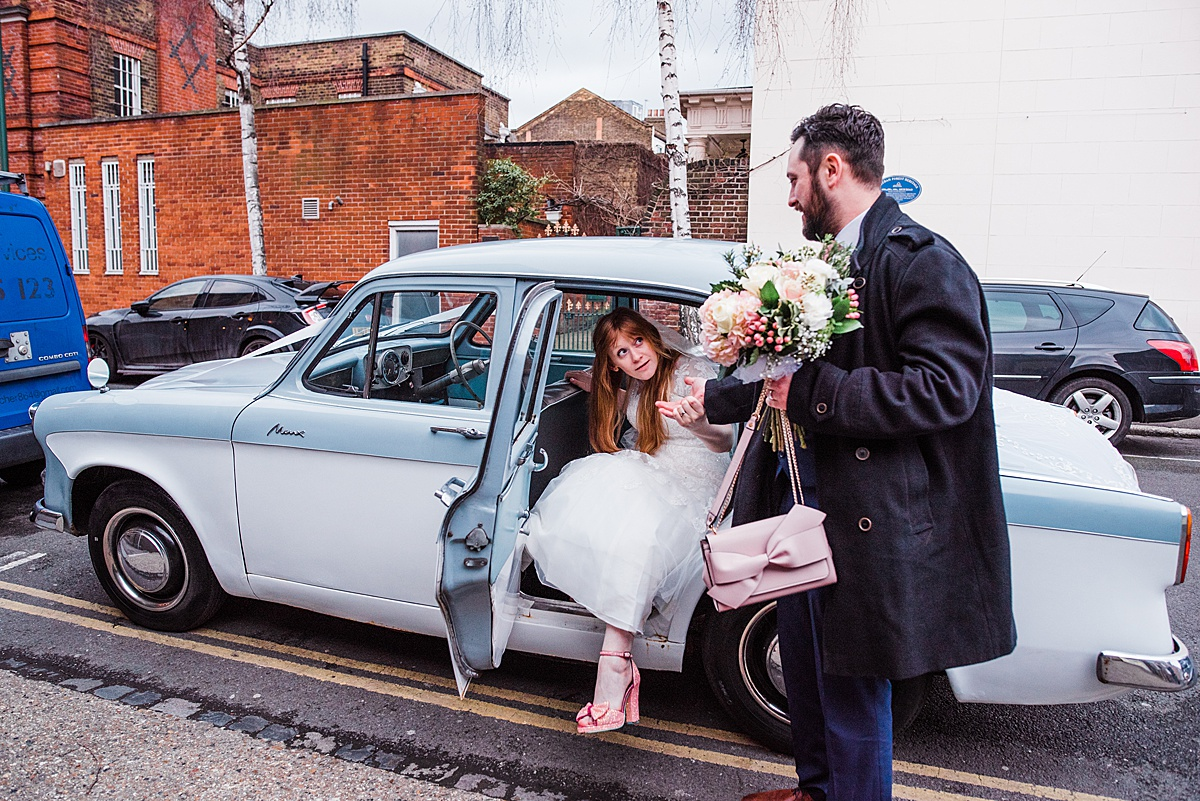 The Groom Aaron helping Bride Kat get out of their vintage wedding car - Photo taken by Parrot and Pineapple Wedding Photography