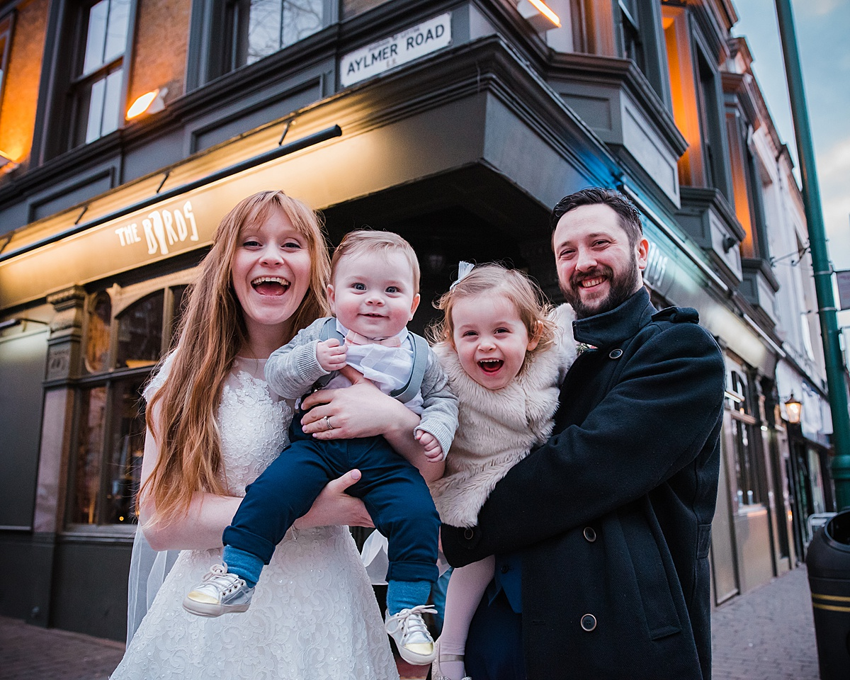 Kat & Aaron with their two children outside The Birds Pub - photo taken by Parrot and Pineapple Wedding Photography