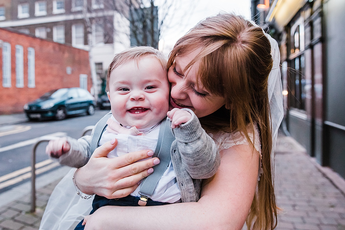 The bride with her son having a cuddle outside The Birds pub - Photo taken by Parrot and Pineapple Wedding Photography