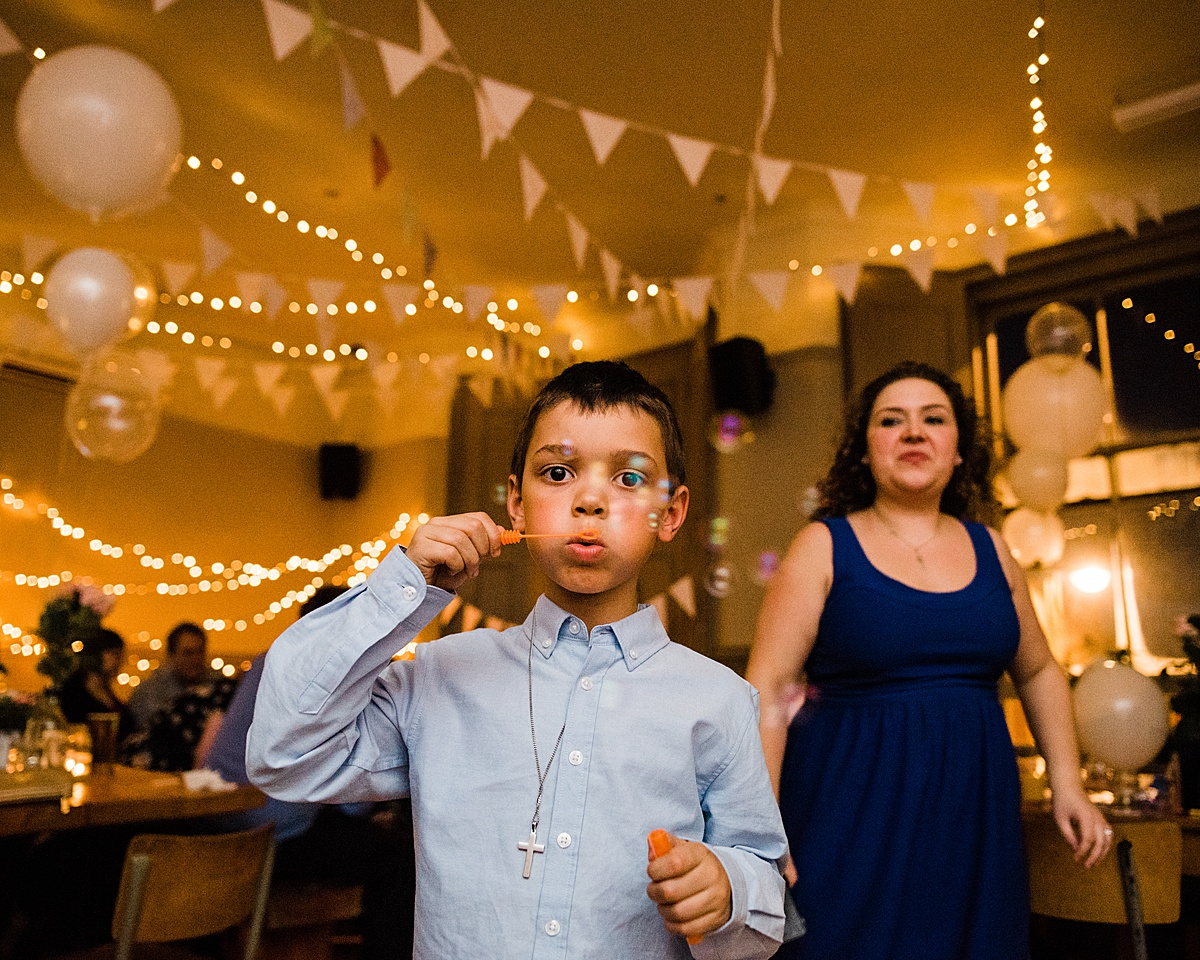 Child wedding guest blowing bubbles at the wedding reception - Photo taken by Parrot and Pineapple Wedding Photography