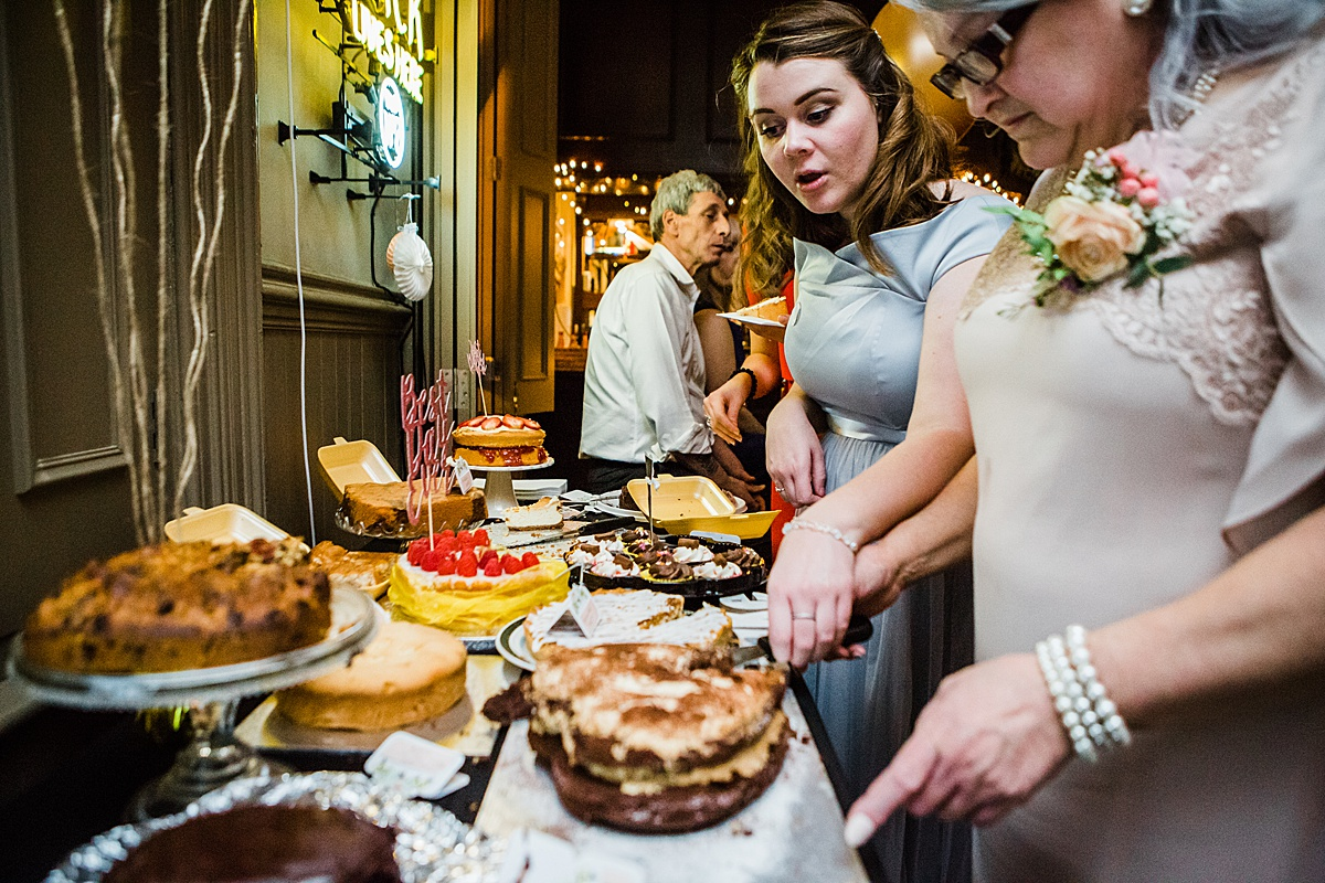 Bridesmaid and guest looking at the buffet at the wedding reception - Photo taken by Parrot and Pineapple Wedding Photography