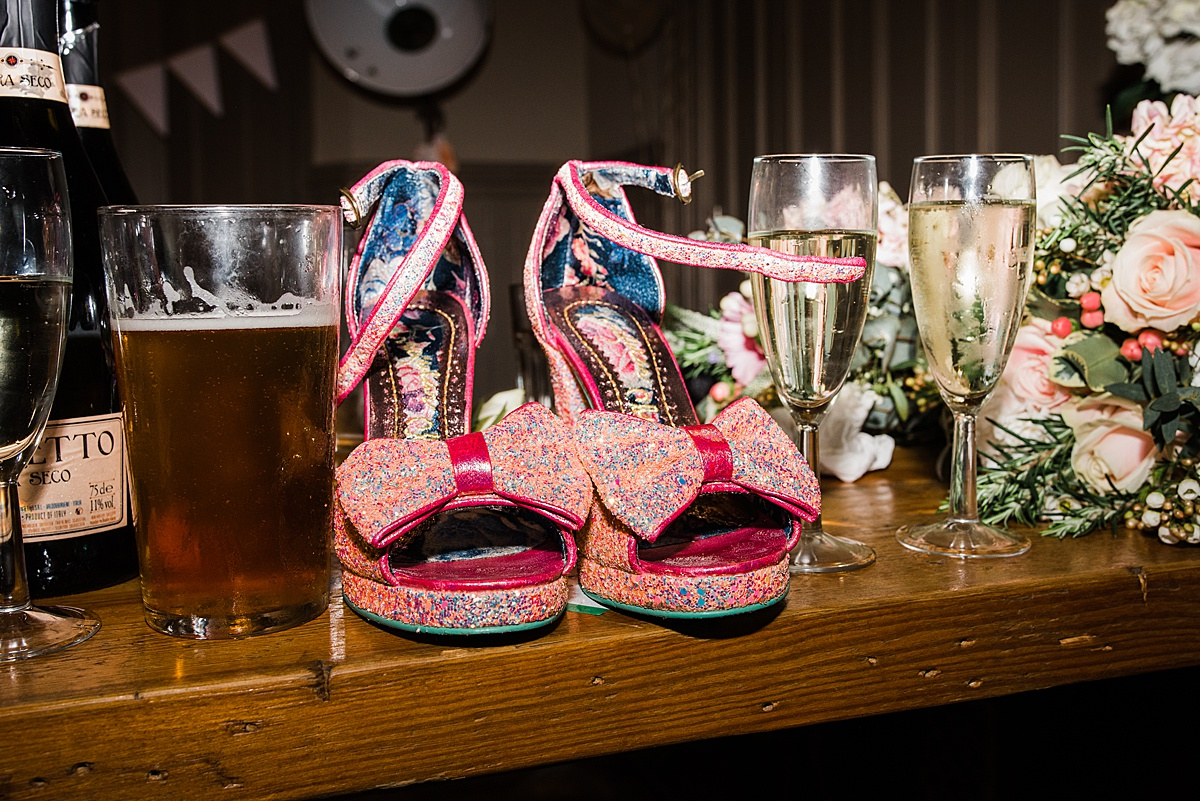 Glittery peep toes wedding shoes on the bar with champagne and a pint - Photo taken by Parrot and Pineapple Wedding Photography