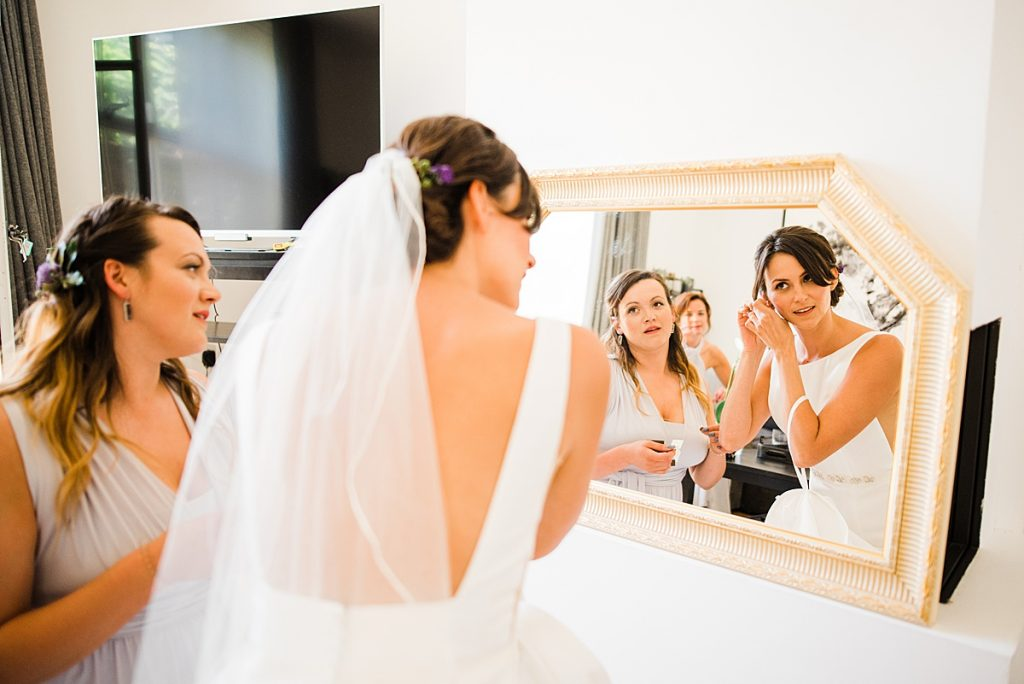 bride putting her earrings in ready to go