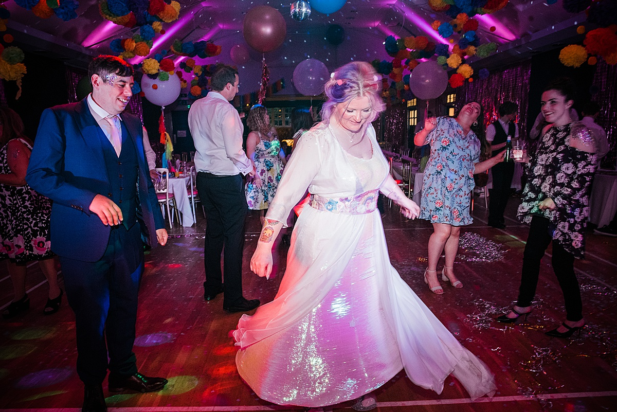 Alternative bridal style. Bride dancing in iridescent sequin wedding gown. Image by Parrot & Pineapple Wedding Photography.