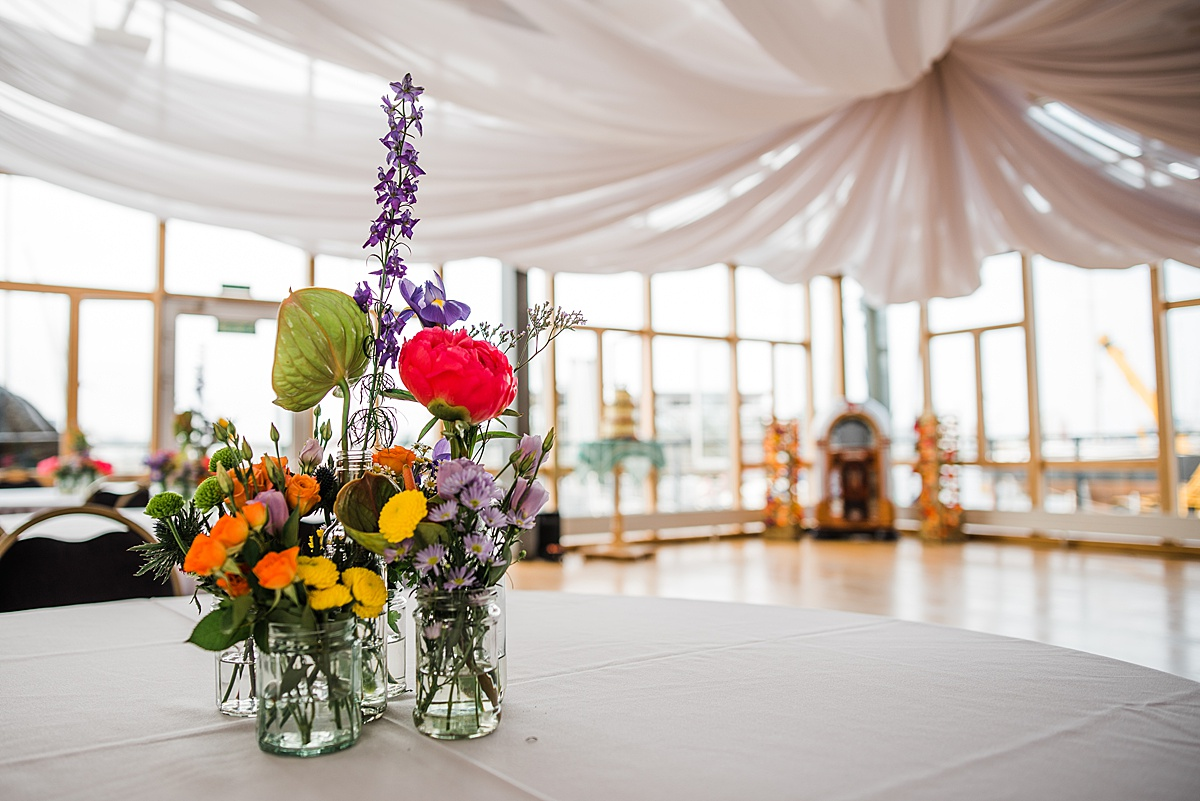 Brightly coloured flowers in jam jar vases at Greenwich Yacht Club wedding. Image by Parrot & Pineapple. Click through to see more brightly coloured wedding photos.