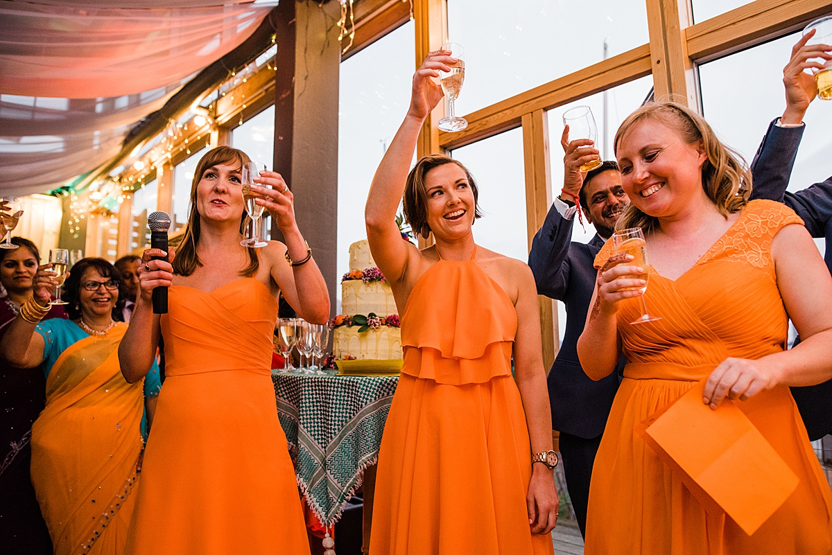 Bridesmaids raise glasses to toast bride and groom at Greenwich Yacht Club wedding. Image by Parrot & Pineapple. Click through to see more brightly coloured wedding photos.