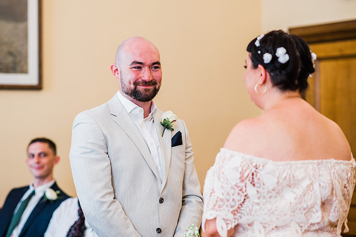 Groom smiles at bride during Islington town hall wedding - Parrot and Pineapple photography