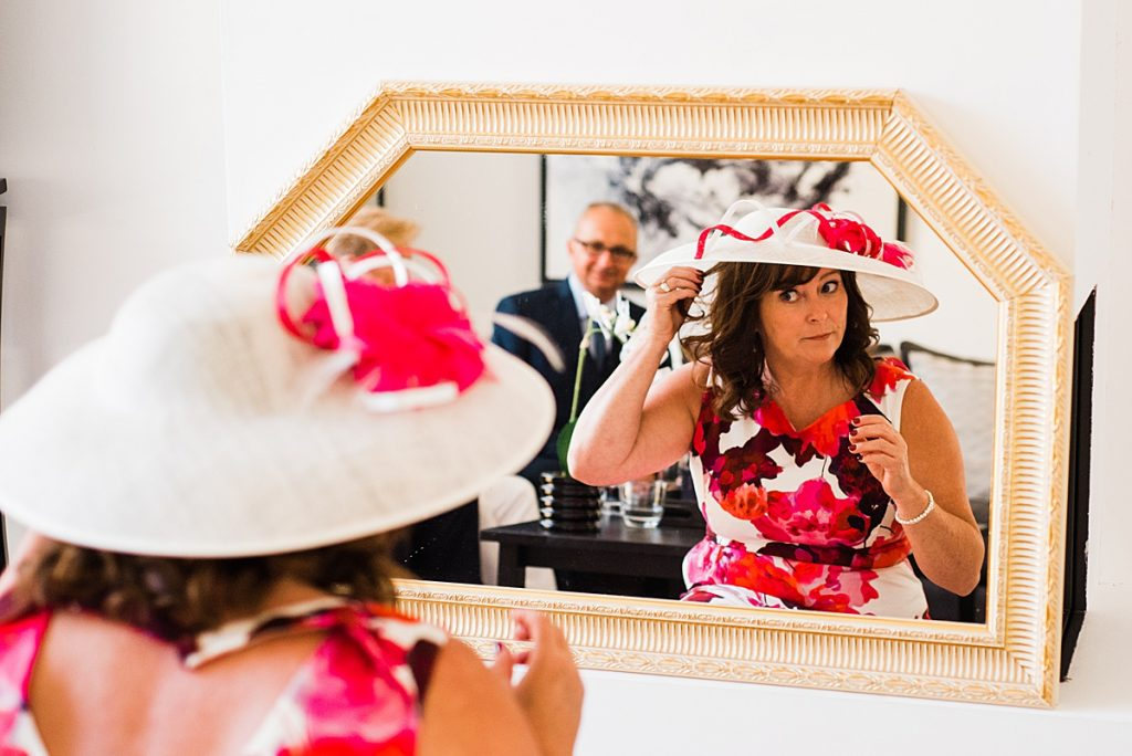 Mother of the Bride getting ready for the wedding in her floral dress and hat