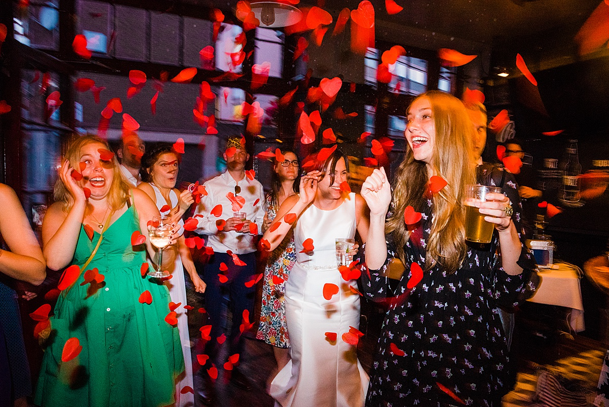 Red confetti r aining down on a bride and her friends at the wedding party. Image by Parrot and Pineapple.