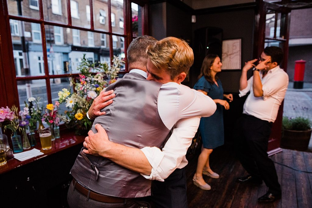 groomsmen embrace on the dance floor