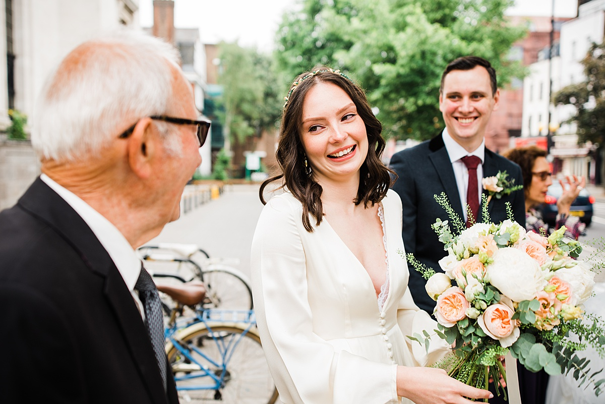 bride smiles at elderly relative outside islington town hall  - parrot and pineapple wedding photography