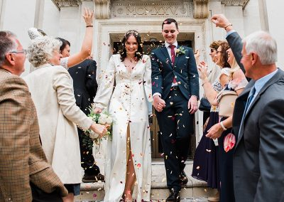 bride and groom walk under confetti shower outside islington town hall - Parrot and pineapple
