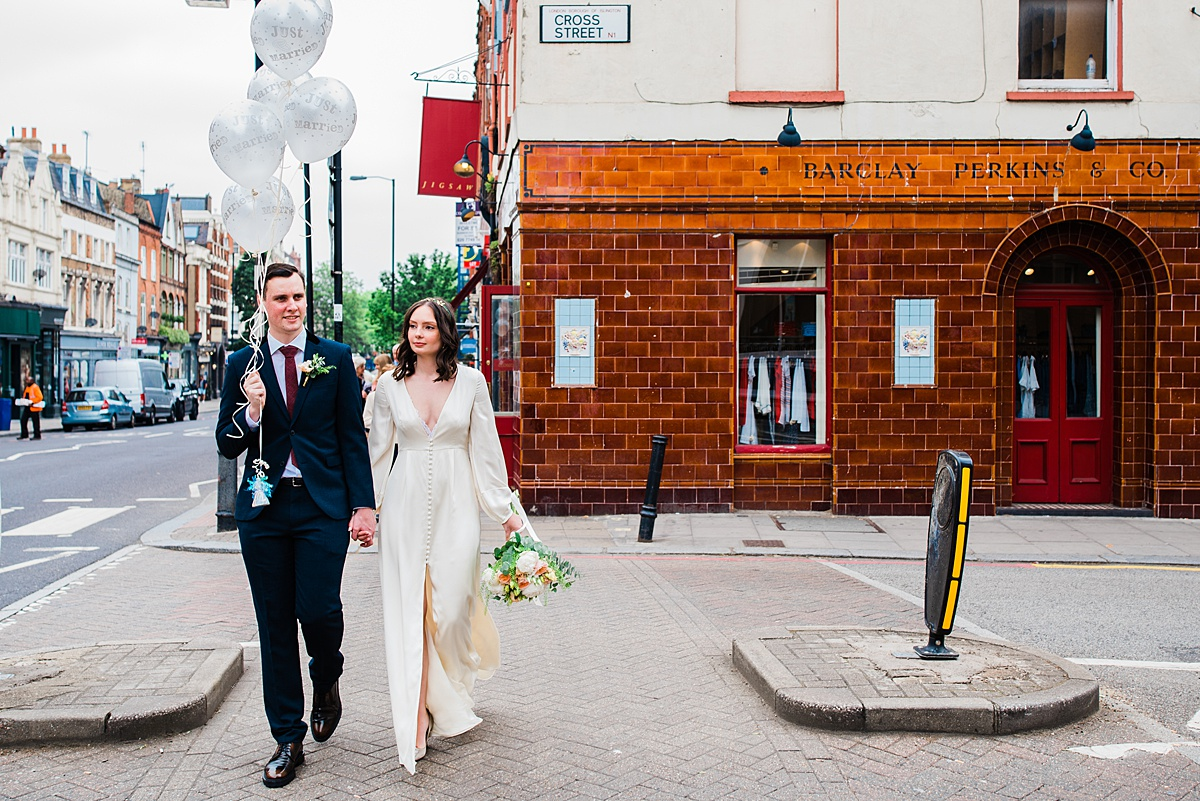 Bride and groom hold balloons crossing the road  - parrot and pineapple wedding photography